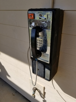 a weathered, wall-mounted payphone